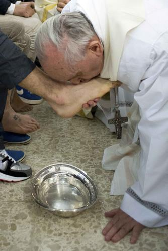 Pope Francis kissing inmates' feet.