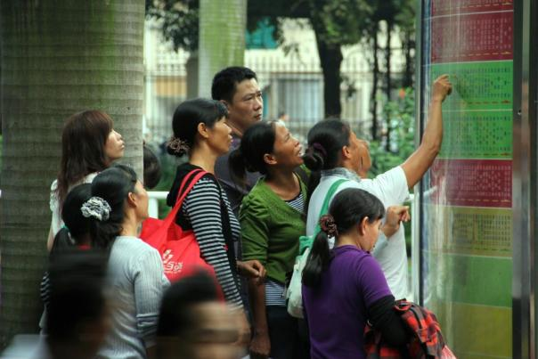 Even locals have to study the bus routes in Nanning!  Photo by Evan Schneider.